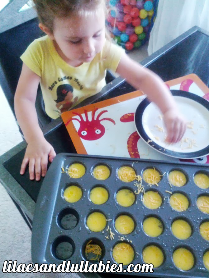 Lelia sprinkling cheddar cheese on egg mini muffins